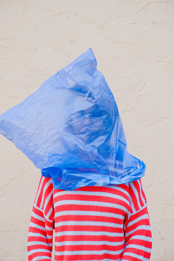 Young woman with a blue plastic bag on her head, dressed in a striped red and white jumper - gettyimageskorea