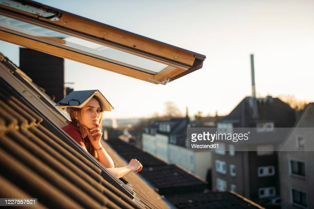 young woman with a book on her head at the window - roof stock pictures, royalty-free photos & images