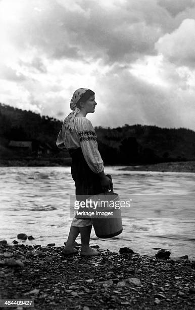 Young woman with a bucket Bistrita Valley Moldavia northeast Romania c1920c1945 Depicting customs and traditional labour in the rural Carpathian...