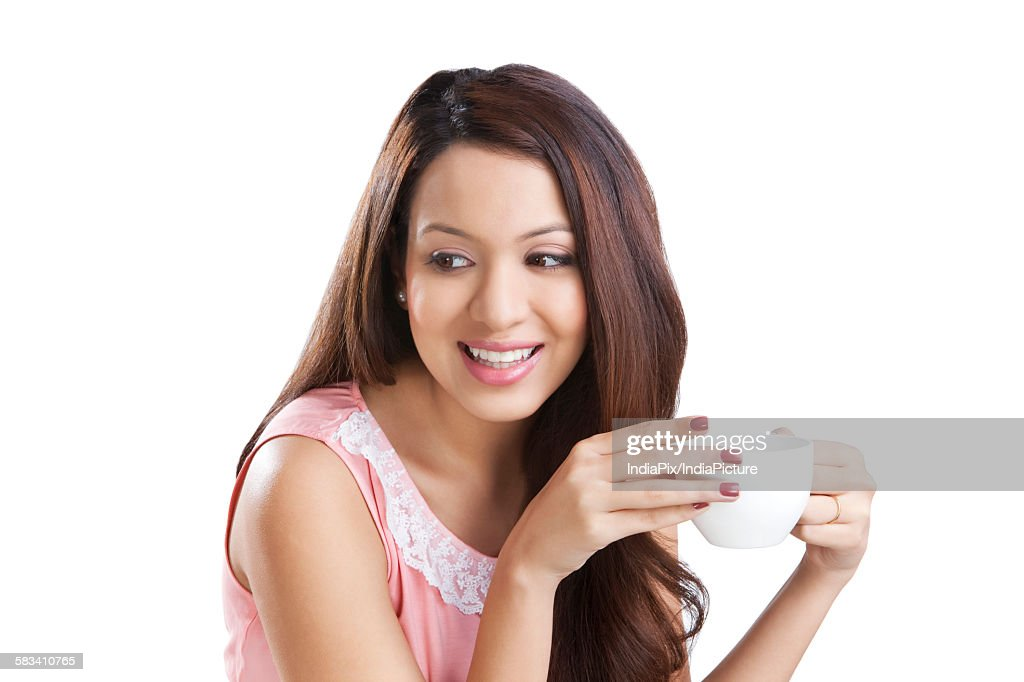 Young woman with a coffee cup smiling : Stock Photo