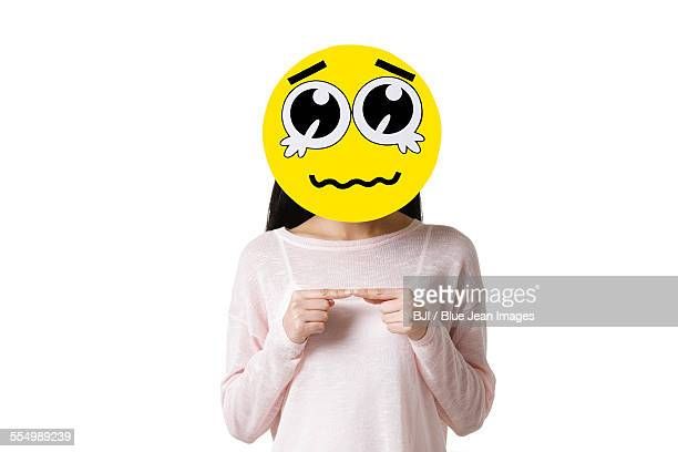 Young woman with a crying emoticon face in front of her face
