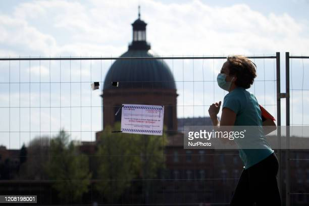 A young woman with a face mask does jogging on a sunny day in Toulouse with the touristic Dome de la Grave in the backgroundThe placard reads...