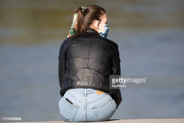Young woman with a face mask is seen along the left bank of the Vistula river in Warsaw, Poland on April 20, 2020. As Poland on Sunday reached it's...