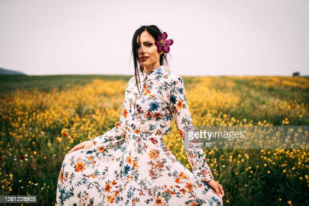 young woman with a flower in her hair relaxing in nature - floral pattern dress stock pictures, royalty-free photos & images