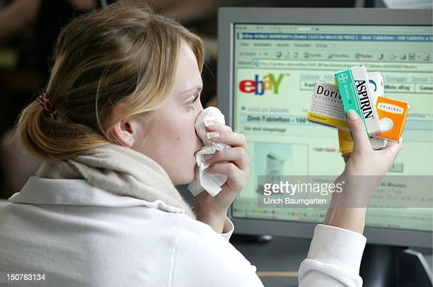 Young woman with a flu holding medicine and looking at the Internet site of the online auctioneers eBay