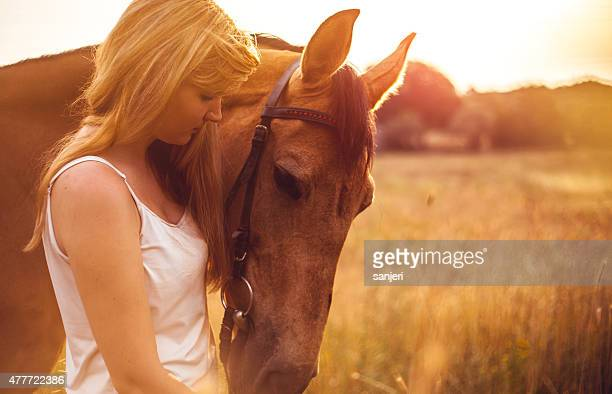 Young woman with a horse in nature