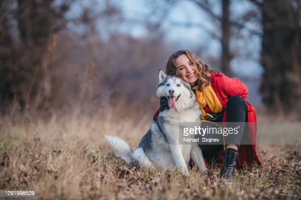屋外でハスキー犬を持つ若い女性 - シベリアンハスキー ストックフォトと画像