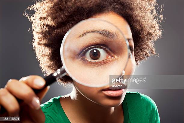 young woman with a loupe - magnifying glass stock pictures, royalty-free photos & images