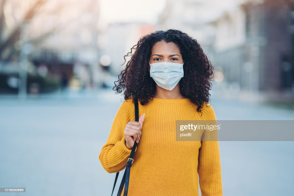 Young woman with a mask during pandemic : Stock Photo