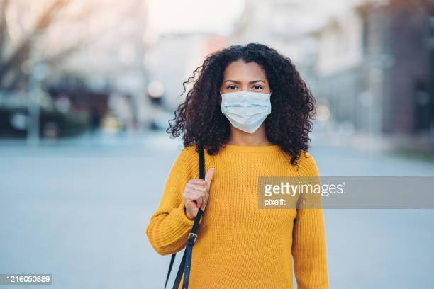 young woman with a mask during pandemic - pandemic illness stock pictures, royalty-free photos & images