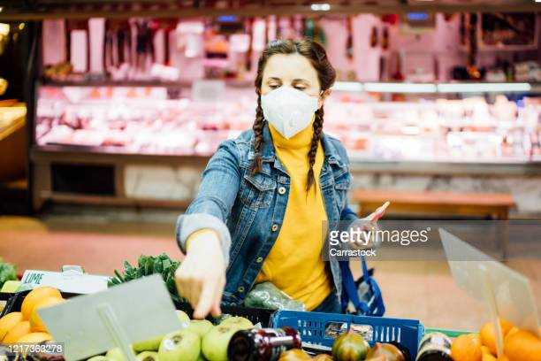 young woman with a mask shopping at a greengrocer's - spain stock pictures, royalty-free photos & images