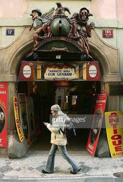 A young woman with a mobile phone walks past the entrance to marionette theatre advertising a performance of Wolfgang Amadeus Mozart's 'Don Giovanni'...