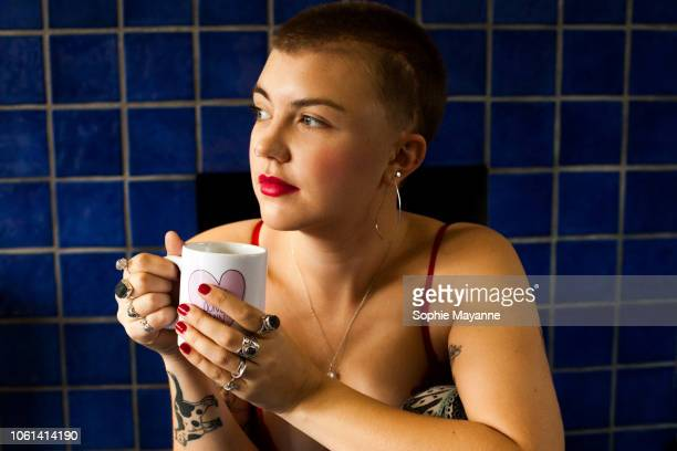 A young woman with a mug sat looking to the side