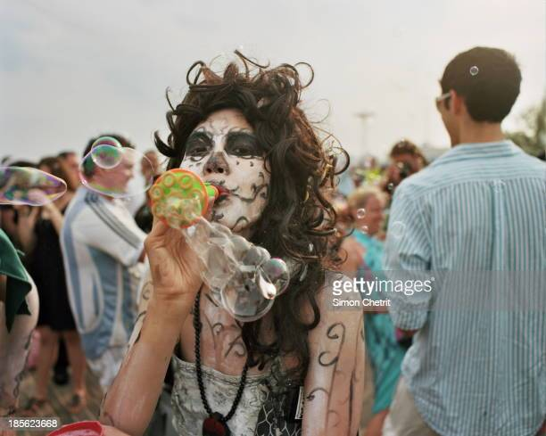 CONTENT] A young woman with a painted face participates in a Bubble Battle on Coney Island's boardwalk