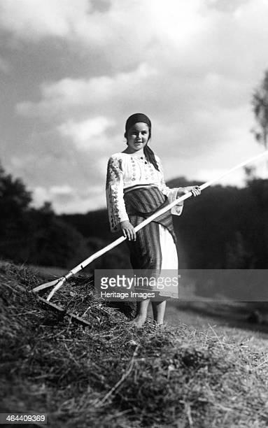 Young woman with a rake Bistrita Valley Moldavia northeast Romania c1920c1945 Depicting customs and traditional labour in the rural Carpathian...