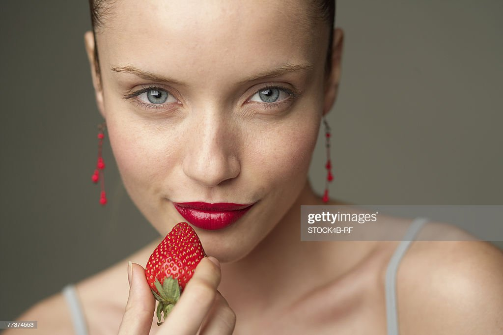 Young woman with a red strawberry under her red lips (part of), close-up : Stock Photo