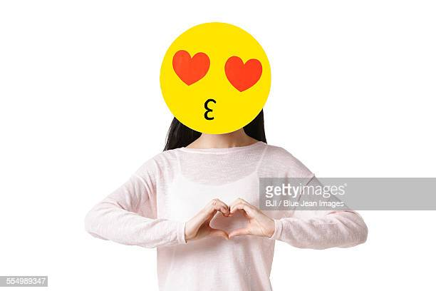 Young woman with a romantic emoticon face in front of her face