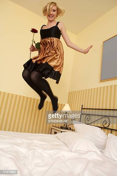 Young woman with a rose jumping on a bed