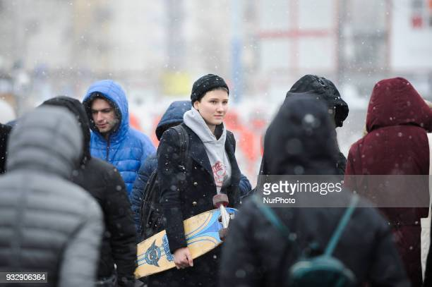 A young woman with a skateboard is seen amongst pedestrians near the central metro station in Warsaw Poland on March 16 2018 After a spell of warm...