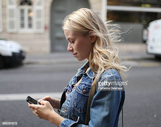 a young woman with a smartphone in the street - cheveux blonds photos et images de collection