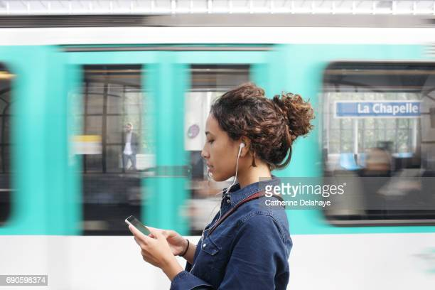 a young woman with a smartphone in the subway of paris - 地下鉄 ストックフォトと画像