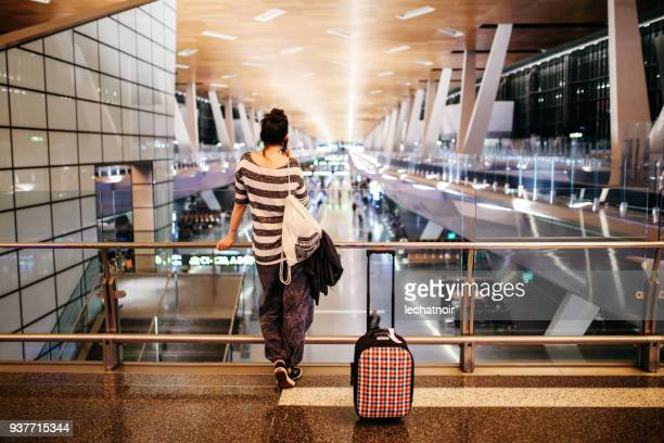 young woman with a suitcase traveling solo on the qatar airport - doha stock pictures, royalty-free photos & images
