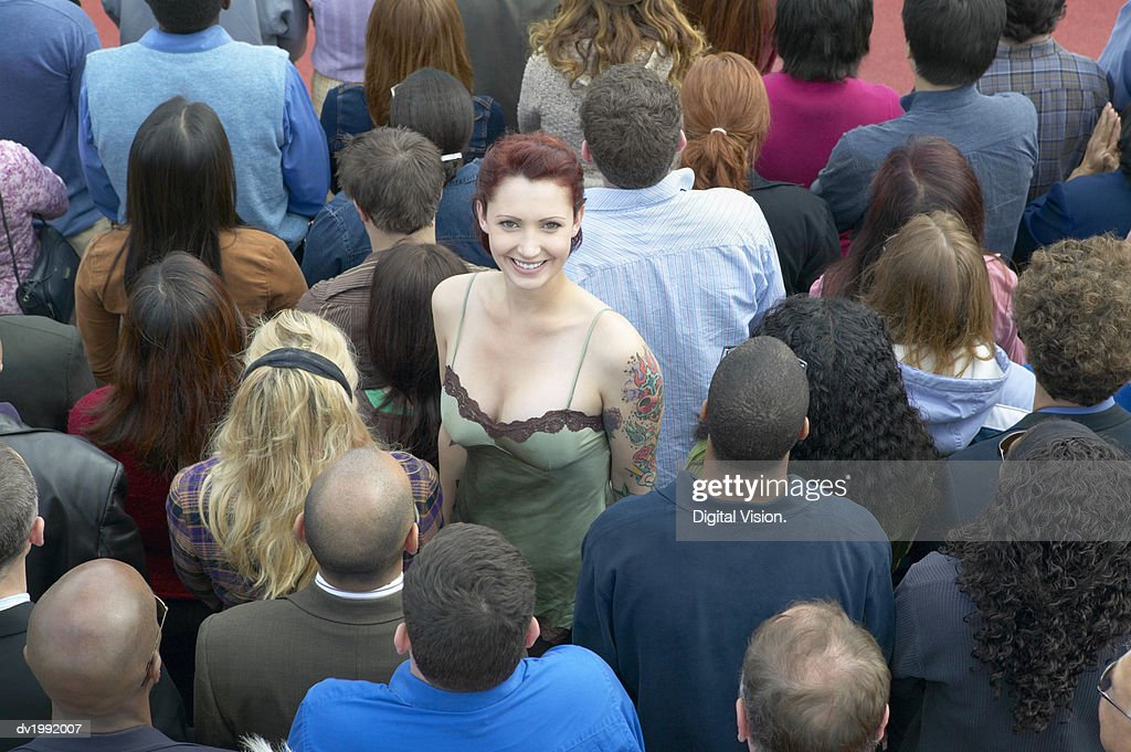 Young Woman with a Tattoo Standing Out From a Crowd of People with Their Back Turned : Stock Photo