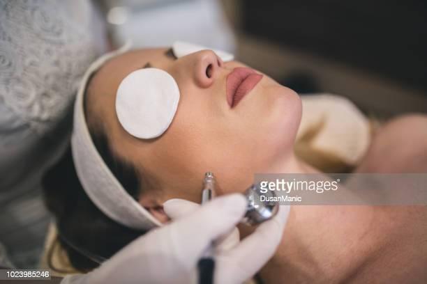 mujer joven con una toalla en la cabeza acostado sobre una mesa con los ojos cerrados recibiendo un tratamiento láser de la piel en el salón de spa de belleza saludable - depilacion laser fotografías e imágenes de stock
