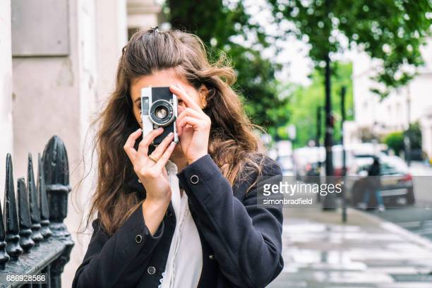 young woman with a vintage camera - photographic film camera stock photos and pictures