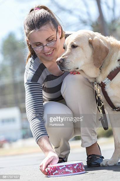 Young woman with a visual impairment feeding her service dog