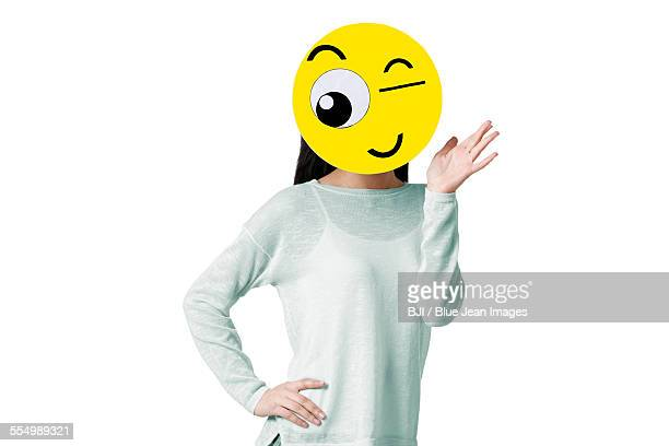 Young woman with a winking emoticon face in front of her face