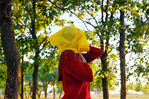 Young woman with a yellow bag on her head and in a red jumper on a background of green trees - gettyimageskorea
