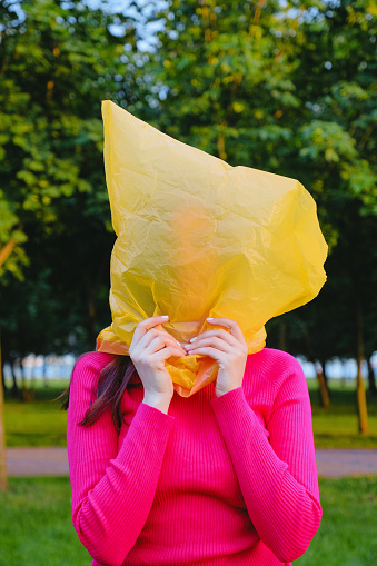Young woman with a yellow plastic bag on her head, dressed in a pink cardigan - gettyimageskorea