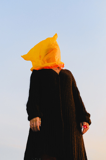Young woman with a yellow plastic bag on her head, dressed in black clothes, against the sky - gettyimageskorea