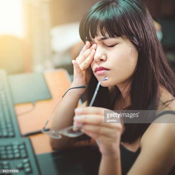 Young woman with aching eyes after working on computer.
