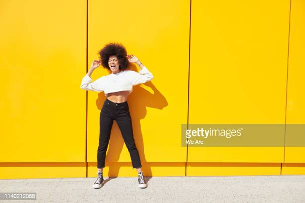 young woman with afro dancing in front of yellow wall - monochrome clothing stock pictures, royalty-free photos & images
