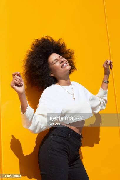 young woman with afro dancing in front of yellow wall - solo una donna giovane foto e immagini stock