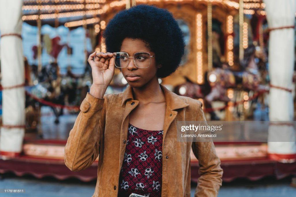 Young woman with afro hair putting on spectacles in front of carousel : Stock Photo