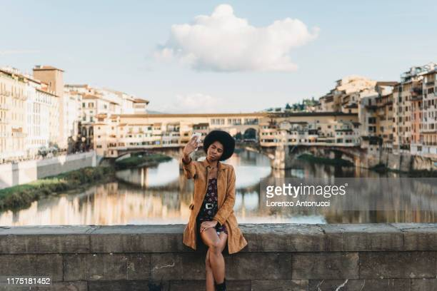 young woman with afro hair taking selfie on bridge, florence, toscana, italy - florence italy foto e immagini stock