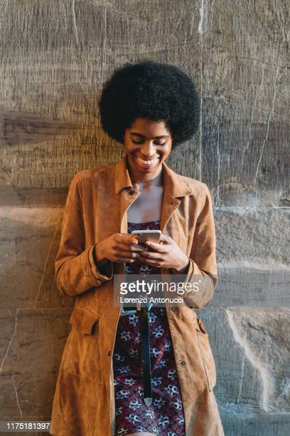 young woman with afro hair using smartphone, leaning against stone wall - mini dress stock pictures, royalty-free photos & images