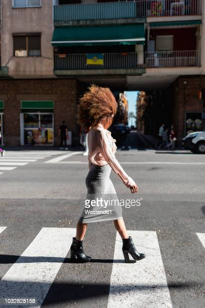 young woman with afro hairdo crossing the street in the city - zebra crossing stock pictures, royalty-free photos & images