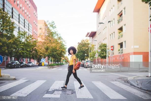 young woman with afro hairdo walking in the city - zebrapad stockfoto's en -beelden
