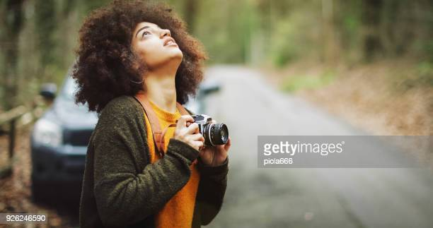 young woman with afro hairstyle taking photos in the woods - 4k resolution stock pictures, royalty-free photos & images