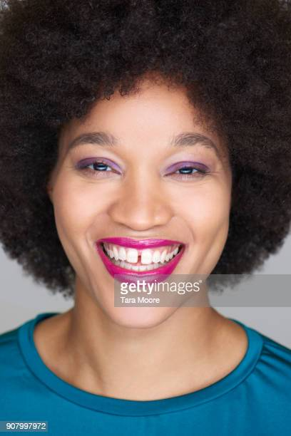 young woman with afro smiling - pink lipstick stock photos and pictures