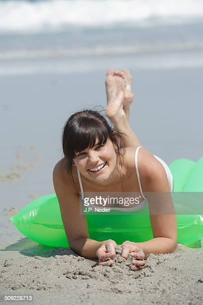 young woman with air mattress on the beach - soles pose stockfoto's en -beelden