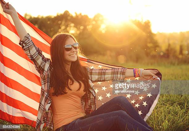 young woman with an American flag on the nature
