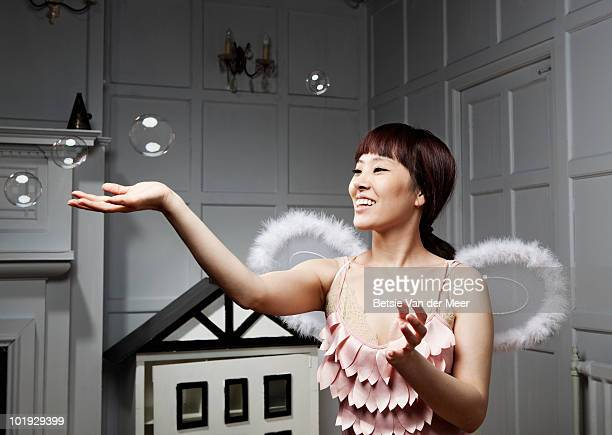 Young woman with angle wings touching bubbles.