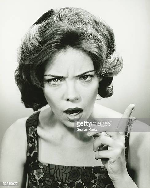 Young woman with angry look, scolding, posing in studio, (B&W), portrait