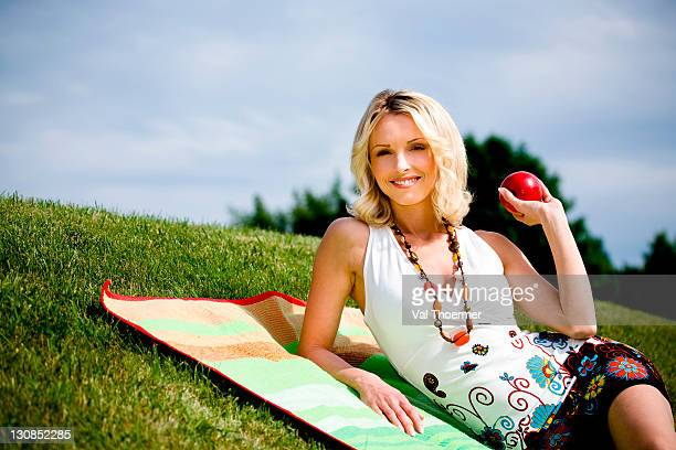 Young woman with apple in a meadow