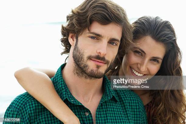 Young woman with arm around boyfriend, portrait